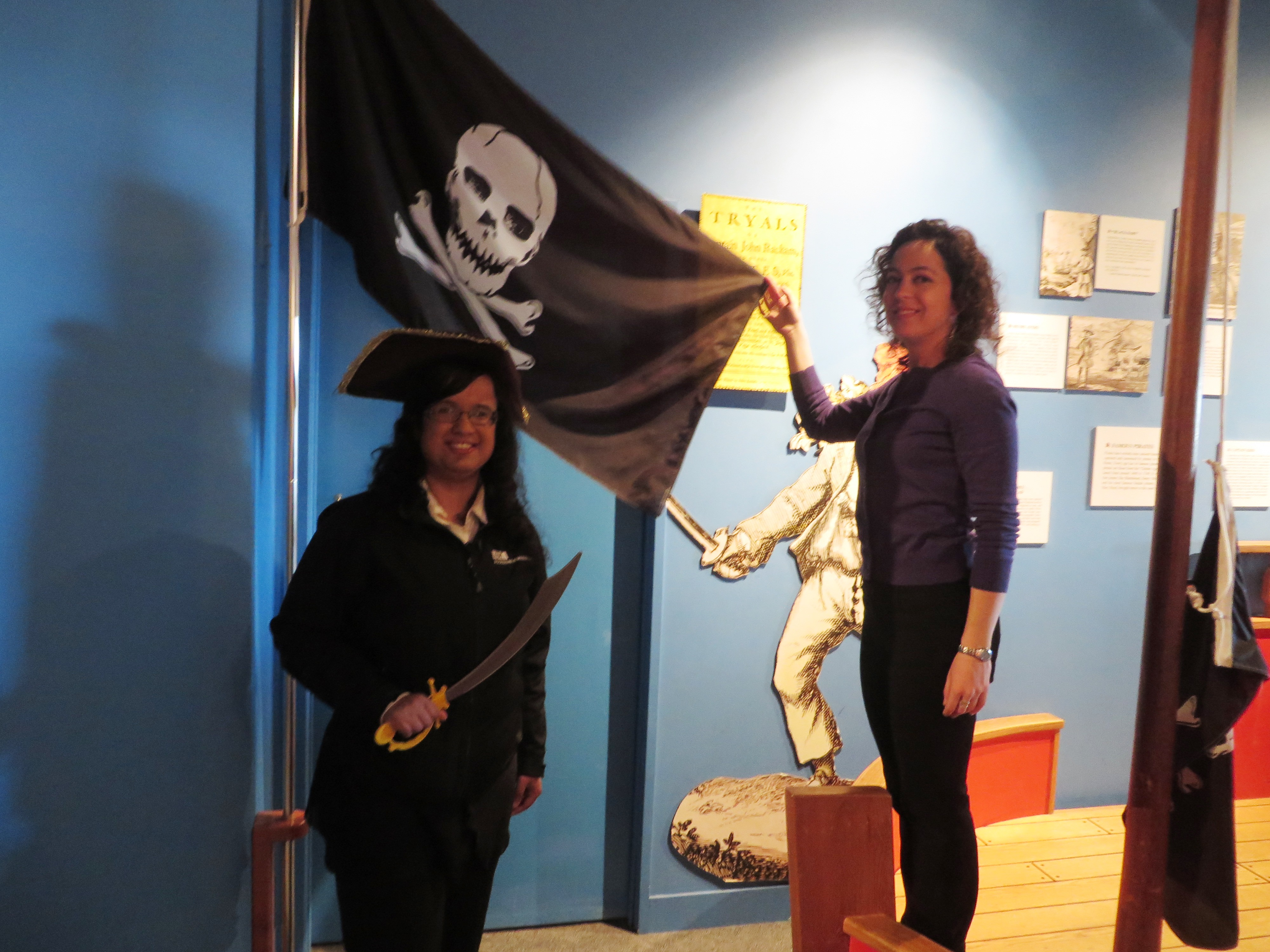 Kristy dressed as a pirate, standing in front of a jolly roger pirate flag